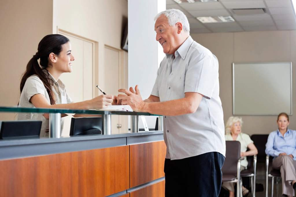 Receptionist helping a customer to get accommodation at an establishment.